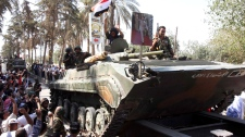 In this photo taken on a government-organized tour, Syrian soldiers salute residents as they sit atop their armored personnel carrier on their way out of the eastern city of Deir el-Zour, Syria, Tuesday, Aug. 16, 2011. (AP / Bassem Tellawi)