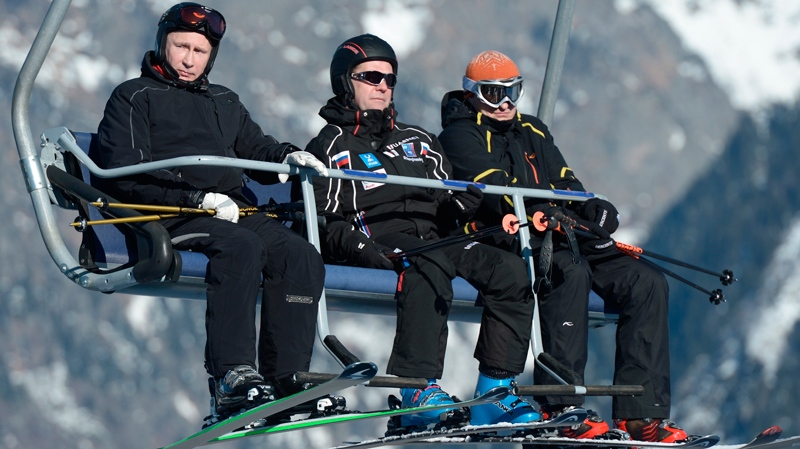 Russian Prime Minister Dmitry Medvedev, centre, and President Vladimir Putin, left, look around whilst sitting on a ski lift at the mountain resort of Krasnaya Polyana near the Black Sea resort of Sochi, southern Russia, Friday, Jan. 3, 2014. (RIA-Novosti, Alexei Nikolsky / Presidential Press Service)