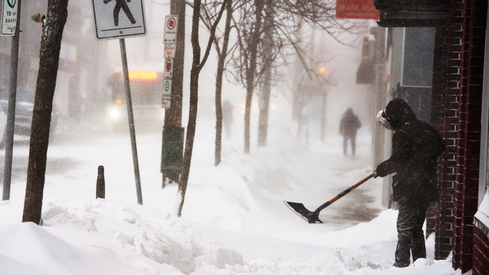 A man clears a sidewalk in blizzard conditions in Halifax on Friday, Jan. 3, 2014. (Andrew Vaughan / THE CANADIAN PRESS)