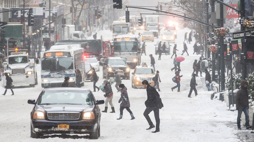 Pedestrians brave wind and snow as they cross Fifth Avenue, Friday, Jan. 3, 2014, in New York. (AP / John Minchillo)