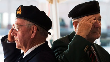 Retired navy Cmdr. Wendall Brown, left, and retired army Lt.-Col. Russ Comeau salute during the playing of the national anthem at a ceremony in Halifax on Tuesday, Aug. 16, 2011. (Andrew Vaughan / THE CANADIAN PRESS)
