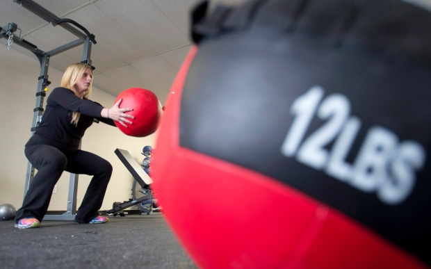 General manager Brianne Angus does squats holding a medicine ball at Downsize Fitness in Orleans, Ont., Tuesday, Dec. 17, 2013. (Adrian Wyld / THE CANADIAN PRESS)
