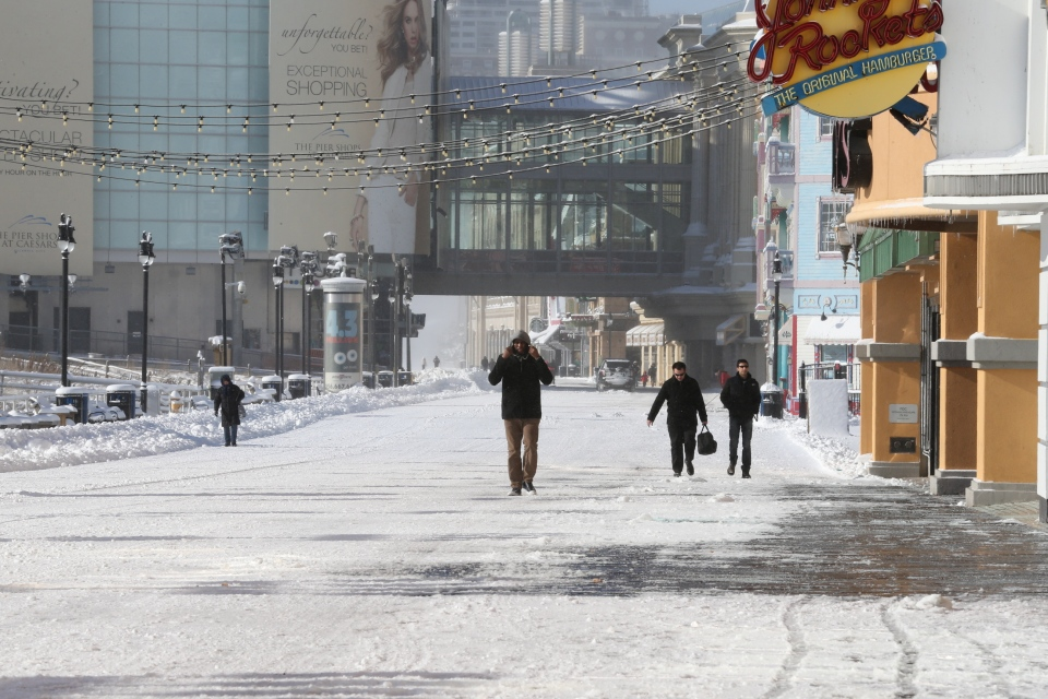 Pedestrians walk along the snow-covered Boardwalk in Atlantic City, N.J., Friday, Jan. 3, 2014. (The Press of Atlantic City / Edward Lea)