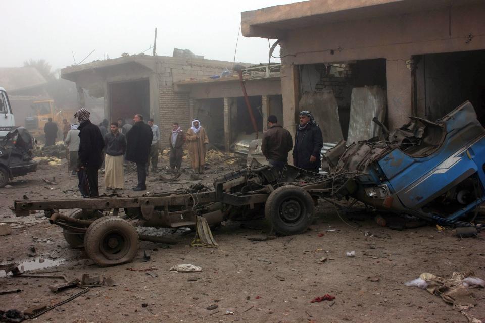 Civilians inspect the aftermath of a massive bomb attack in Balad Ruz, 70 kilometres northeast of Baghdad, Iraq, Friday, Jan. 3, 2014. (AP Photo)