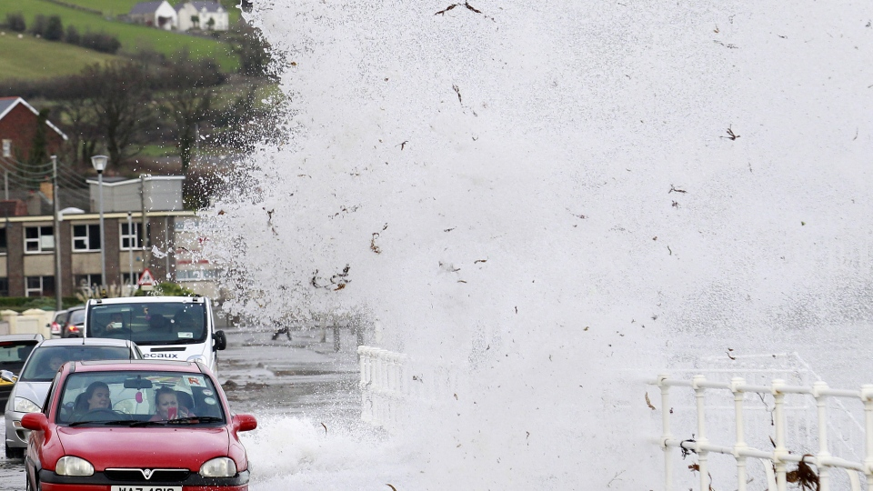 Large waves crash onto the road in the coastal village of Carnlough, Northern Ireland, Friday, Jan. 3, 2014. (AP / Peter Morrison)
