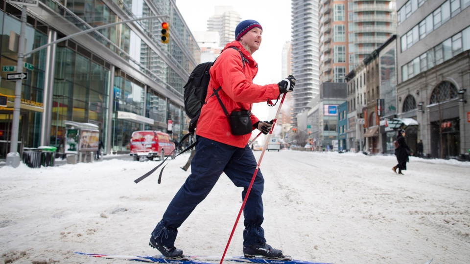 A pedestrian uses his cross-country skis on 58th Street during his morning commute, Friday, Jan. 3, 2014, in New York. New York City public schools were closed Friday after up to 7 inches of snow fell by morning in the first snowstorm of the winter. (AP / John Minchillo)