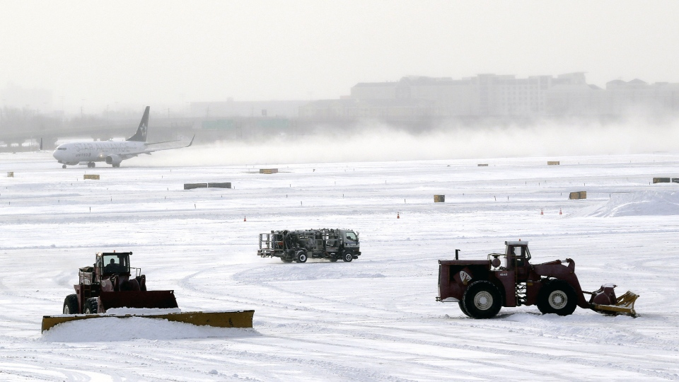A plane takes off from Newark Liberty International Airport as workers plow the tarmac in Newark, N.J. on Friday, Jan. 3, 2014. (AP / Julio Cortez)