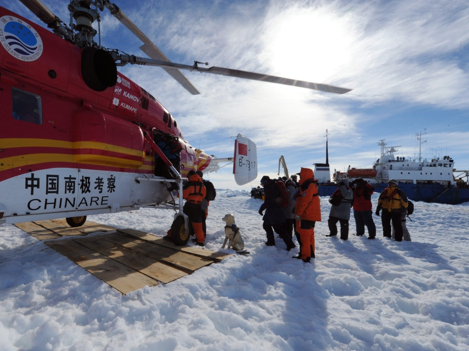 Passengers from the trapped Russian vessel MV Akademik Shokalskiy, seen at right, prepare to board the Chinese helicopter Xueying 12 in the Antarctic Thursday, Jan. 2, 2014. (Xinhua, Zhang Jiansong)
