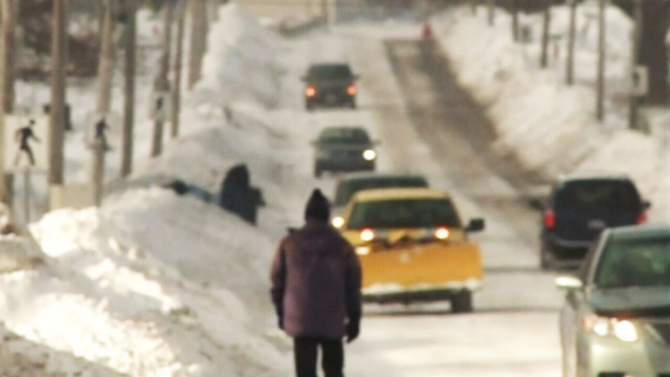 A person walks down the street past sidewalks covered in snow in Glace Bay, N.S. on Saturday, Jan. 4, 2014.