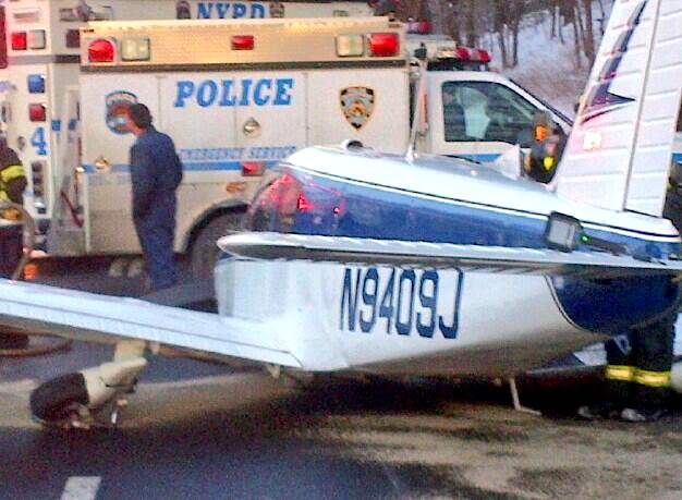 A light airplane's fuselage rests on the roadway after its pilot made an emergency landing on the Major Deegan Expressway in the Bronx borough of New York, Saturday, Jan. 4, 2014. (New York City Police Department / Twitter)