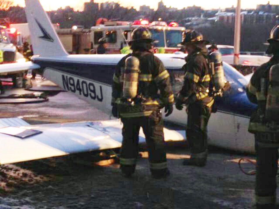 Firefighters stand near a light airplane that made an emergency landing on the Major Deegan Expressway in the Bronx borough of New York, Saturday, Jan. 4, 2014. (New York City Fire Department / Twitter)