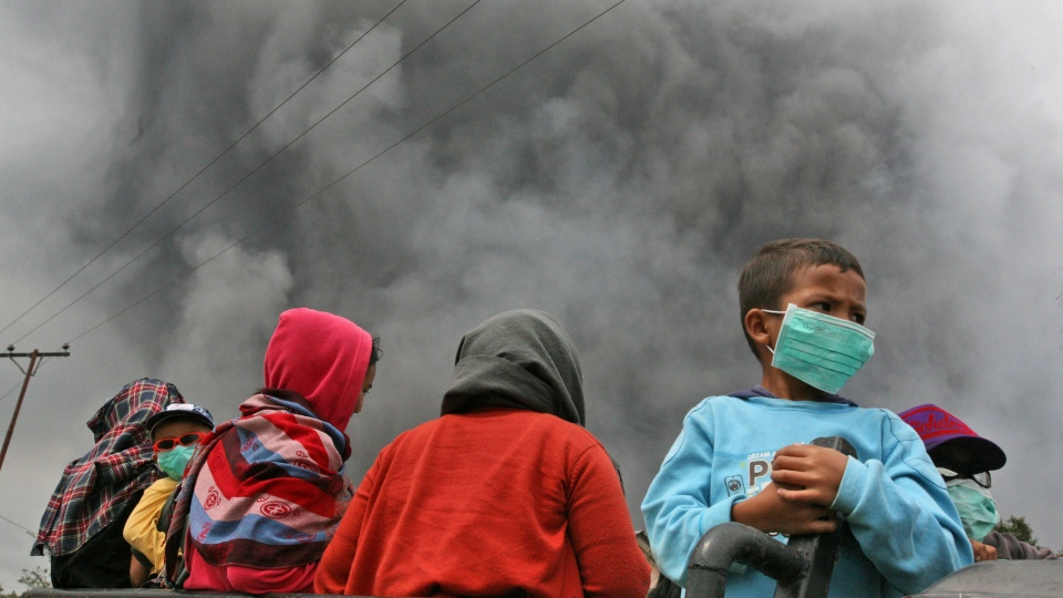 Villagers ride on a truck as volcanic ash from the eruption of Mount Sinabung is seen in the background in Beras Tepu, North Sumatra, Indonesia, Saturday, Jan. 4, 2014. (AP / Binsar Bakkara)