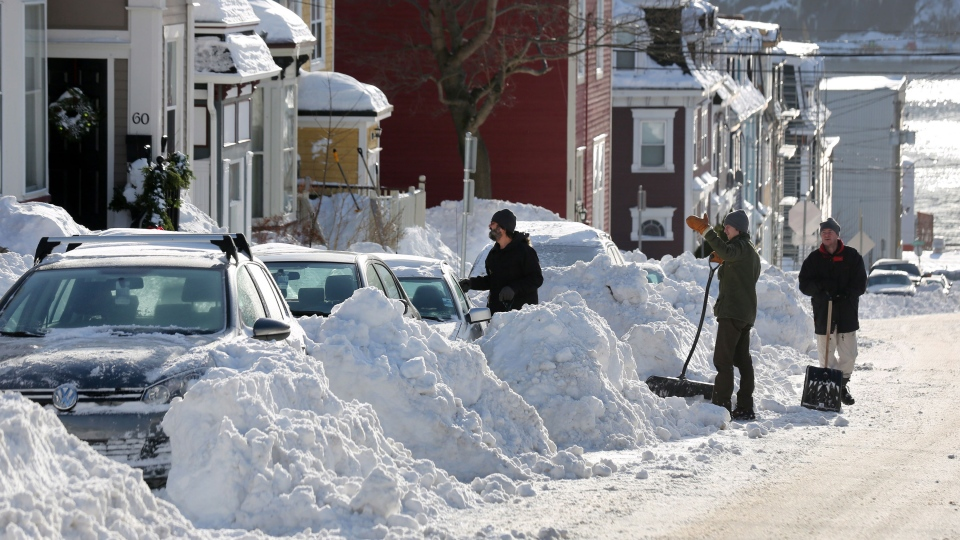 Residents take a break from shovelling snow after a winter storm hit St.John's. N.L., Sunday, Jan.5, 2014. (Paul Daly / THE CANADIAN PRESS)