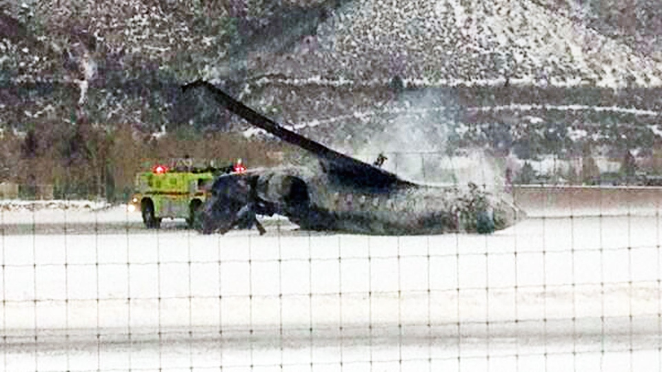 Emergency crews respond as a small plane lies on a runway at Aspen Airport in western Colorado after it crashed upon landing Sunday, Jan. 5, 2014. (AP/Corey Morris-Singer)