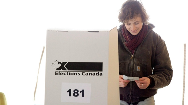 A woman examines her ballot card as she prepares to cast her vote for the federal election in a polling station on Toronto's Ward Island on Monday, May 2, 2011. (Chris Young / THE CANADIAN PRESS)