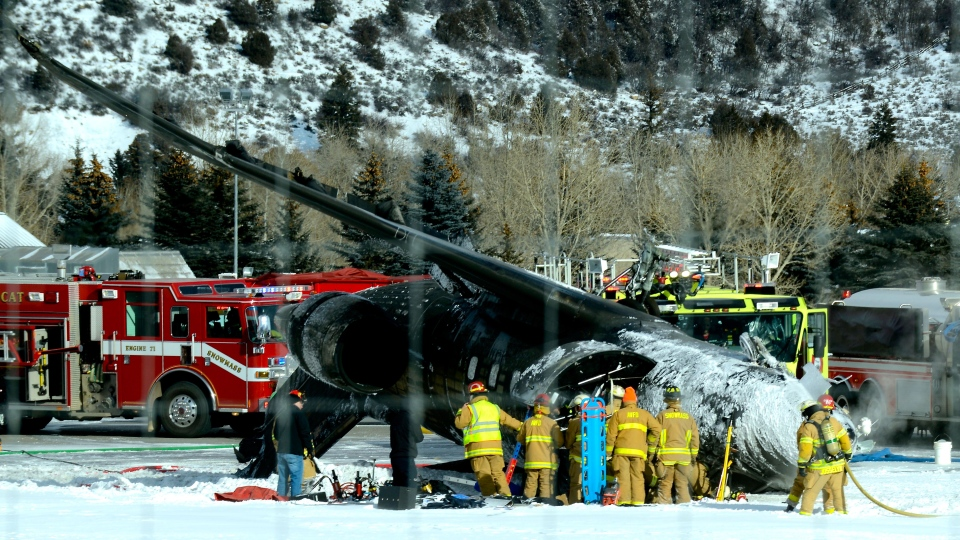 Emergency crews work near a passenger plane that crashed upon landing at the Aspen-Pitkin County Airport in Aspen, Colo., Sunday, Jan. 5, 2014. (The Aspen Times, Leigh Vogel)