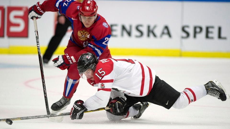 Canada defenceman Derrick Pouliot (15) is run over by Russia forward Andrei Mironov (22) during third period action in the bronze medal game at the IIHF World Junior Hockey Championships in Malmo, Sweden on Sunday, Jan. 5, 2014. (Frank Gunn / THE CANADIAN PRESS)