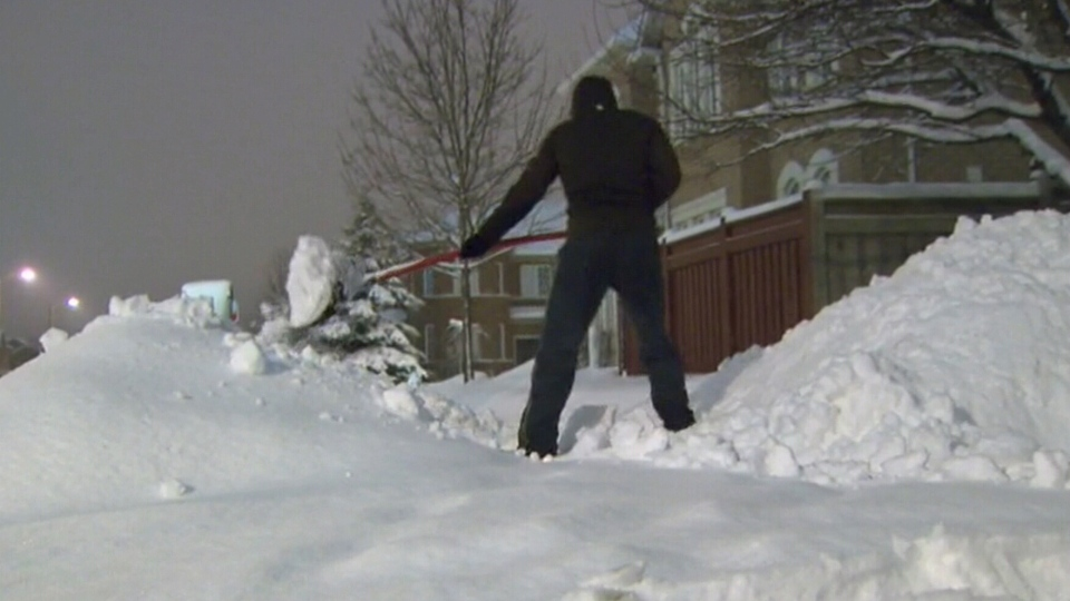 A man shovels the heavy wet snow after southern Ontario got hit with a wet wintery blast, Monday, Jan. 6, 2014.