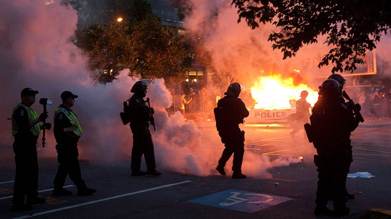 Riot police look on as two police cars burn during a riot in downtown Vancouver, Wednesday, June 15, 2011 following the Vancouver Canucks 4-0 loss to the Boston Bruins in game 7 of the Stanley Cup hockey final. Geoff Howe / THE CANADIAN PRESS
