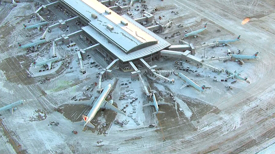 In this aerial view from the CTV News helicopter, snow-clearing crews work as Air Canada flights move in and out of Terminal 1 at Toronto Pearson International Airport, Monday, Jan. 6, 2014.