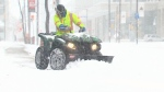 A man clears snow with an ATV in downtown Toronto, Monday, Jan. 6, 2014. Snow, freezing rain and rain created a mess throughout the Greater Toronto Area overnight.