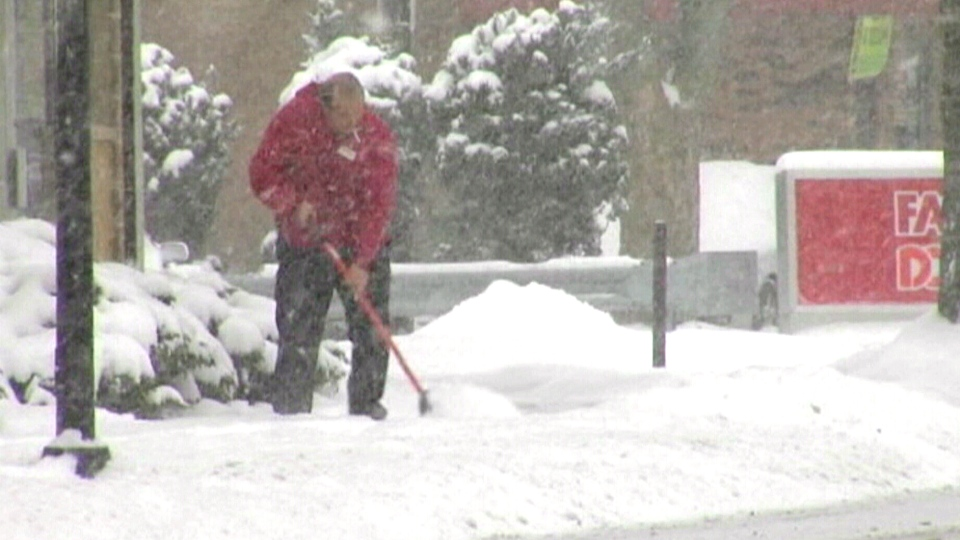 A man shovels snow in Halifax, Monday, Jan. 6, 2014.