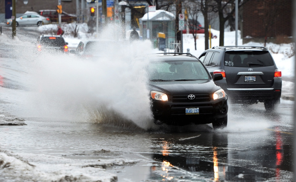Traffic makes its way along a puddle-laden Somerset Street in Ottawa on Monday, Jan. 6, 2014. (Sean Kilpatrick / THE CANADIAN PRESS)