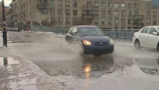 a car splashes through a puddle in Montreal on Jan
