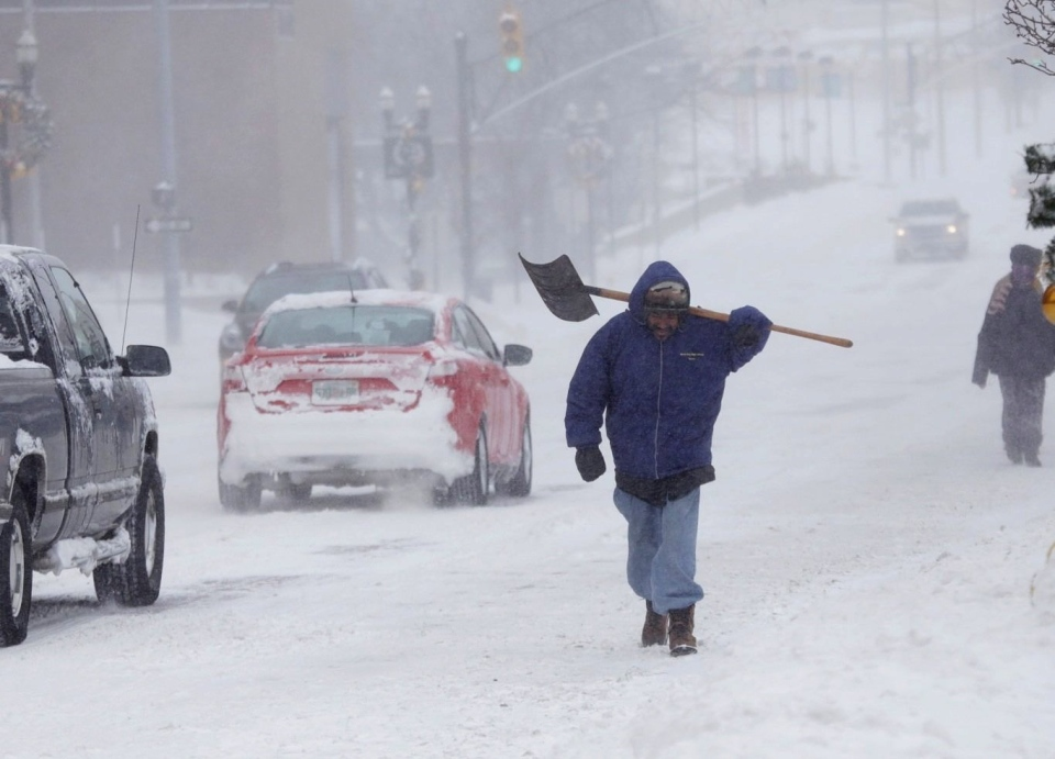 Peter Vasquez of Flint carries his shovel while walking through the drifting snow along a plowed Saginaw Street in downtown Flint, Mich., on Monday Jan. 6, 2014.  (AP / Detroit Free Press, Ryan Garza)
