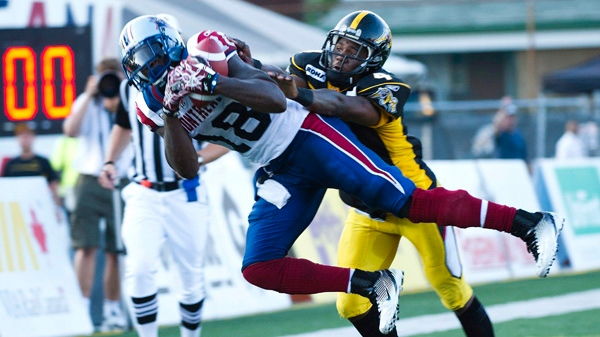 Montreal Alouettes wide receiver Jamel Richardson, left, makes a touch down catch past Hamilton Tiger-Cats defensive back Carlos Thomas, right, during first half CFL football action in Hamilton, Ont., on Friday, July 29, 2011. THE CANADIAN PRESS/Nathan Denette