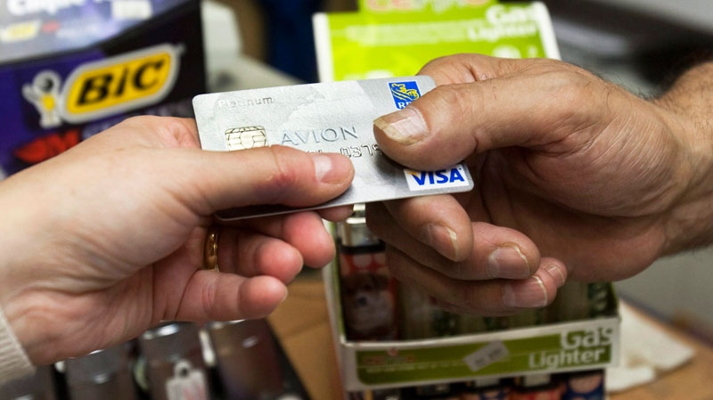 A consumer pays with a credit card at a store Tuesday, July 6, 2010 in Montreal. Ryan Remiorz / THE CANADIAN PRESS
