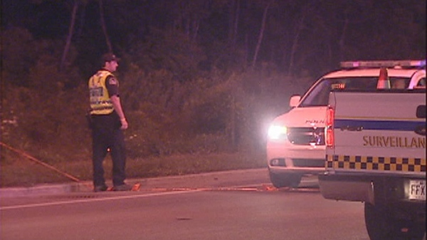 A police officer examines the scene where a motorcycle rider crashed Wednesday night in Terrebonne, north of Montreal (August 17, 2011)