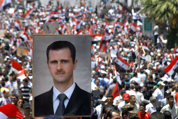 Stephen Harper has joined other world leaders in calling on Syria's president to resign amid a violent crackdown. A protester carries a picture of Syrian President Bashar Assad in Damascus, Syria, Tuesday, June 21, 2011. (AP Photo/Muzaffar Salman)