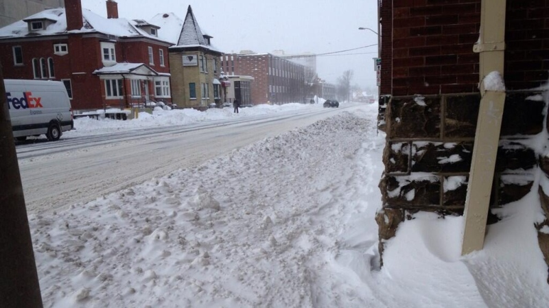 Snow covers a sidewalk on Weber Street in downtown Kitchener, Ont., on Monday, Jan. 6, 2014. (Nicole Lampa / CTV Kitchener)