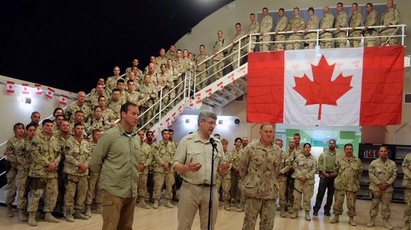 Prime Minister Stephen Harper, middle, talks to media as he is flanked by Chief of the Defence Staff Walter Natynczyk, right, and Minister of Defence Peter MacKay, left, after delivering a speech to Canadian soldiers an civilian at New Canada House at Kandahar Air Field in Afghanistan on Monday, May 30, 2011. Sean Kilpatrick / THE CANADIAN PRESS