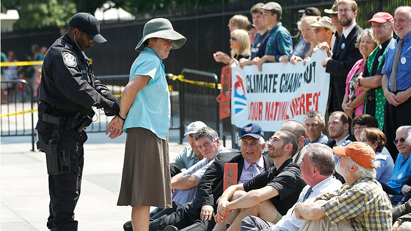 A U.S. Park Police officer handcuffs and arrests a protestor over a proposed pipeline to bring tar sands oil to the U.S. from Canada, in front of the White House in Washington, Saturday, Aug. 20, 2011. (AP / Manuel Balce Ceneta)