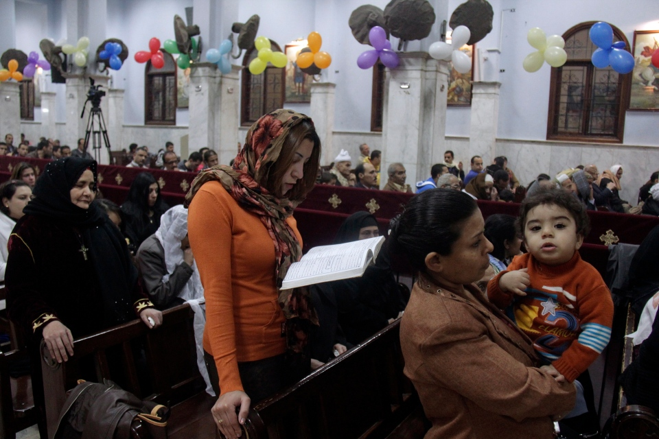 Worshippers attend Orthodox Christmas Eve Mass, where an Oct. 2013 deadly drive-by-shooting killed several at a wedding party, in the Warraq neighborhood of Cairo, Egypt late Monday, Jan. 6, 2014. (AP / Aly Hazzaa, El Shorouk Newspaper)