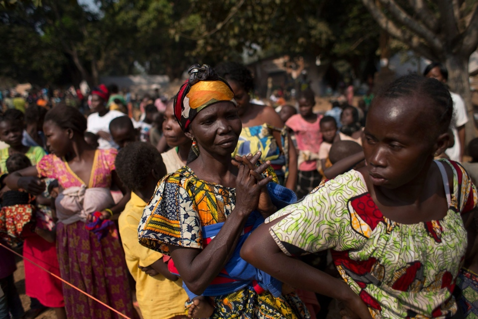 Women wait in line to have their children vaccinated against measles, at a makeshift camp housing people displaced by violence at a monastery in the Boy Rabe district of Bangui, Central African Republic, Sunday, Jan. 5, 2014. (AP / Rebecca Blackwell)
