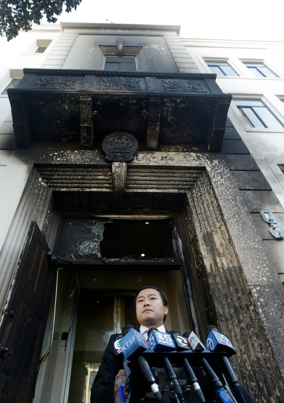 Wang Chuan, spokesperson for the Chinese Consulate, speaks outside of the damaged entrance to the consulate in San Francisco on Thursday, Jan. 2, 2014. The consulate said Thursday that its compound was damaged in an arson attack and urged American authorities to protect the safety of its diplomats and its premises. (AP Photo/Jeff Chiu)