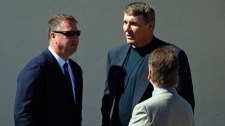 Former NFL quarterback Mark Rypien, centre, talks with Vancouver Canucks general manager Mike Gillis, while attending the funeral service for his cousin Rick Rypien in Blairmore, Alta., Saturday, Aug. 20, 2011. (Jeff McIntosh / THE CANADIAN PRESS)