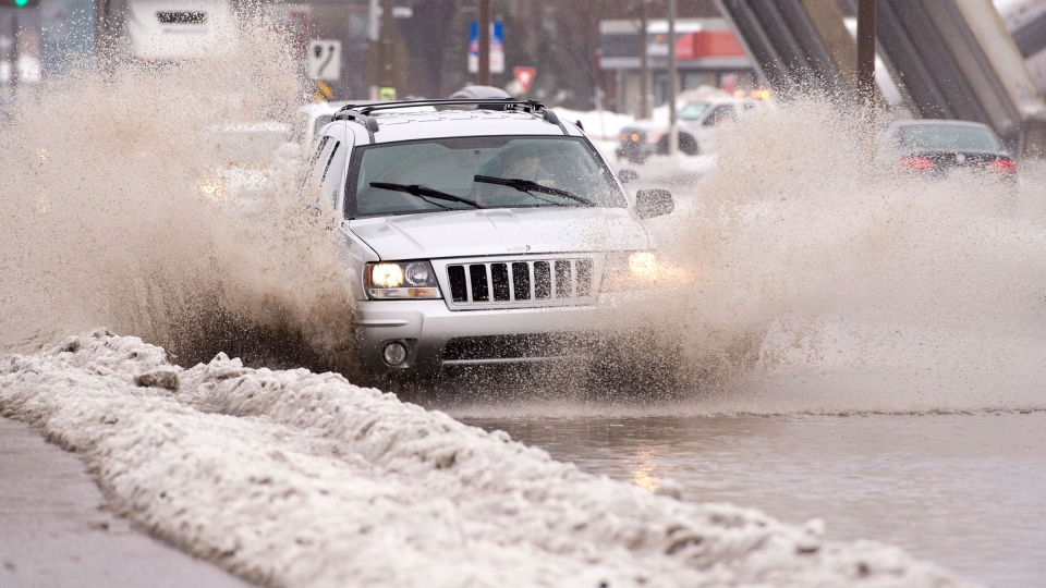 An SUV makes its way through a puddle of water on a main boulevard in Quebec City, Monday, Jan. 6, 2014 (Jacques Boissinot / THE CANADIAN PRESS)