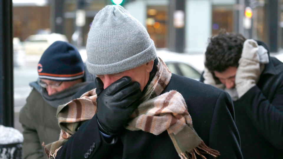 Three men protect themselves from the elements as they walk in Chicago's Loop with temperatures well below zero and wind chills expected to reach 40 to 50 below Monday, Jan. 6, 2014, in Chicago. (AP / Charles Rex Arbogast)