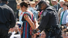 A U.S. Park Police officer handcuffs and arrests a protestor over a proposed pipeline to bring tar sands oil to the U.S. from Canada, in front of the White House in Washington, Saturday, Aug. 20, 2011. (AP Photo/Manuel Balce Ceneta)