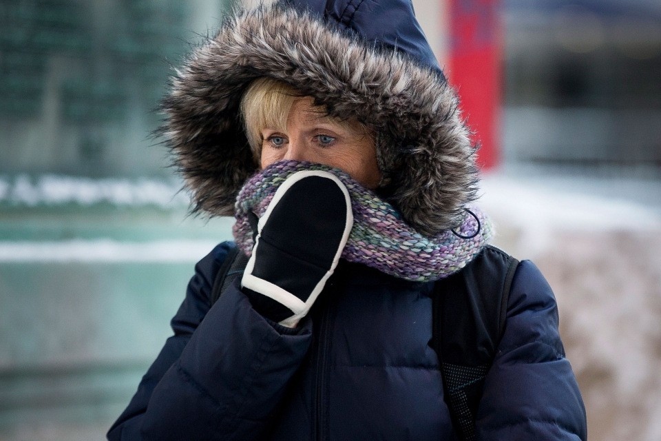 A woman shields her face as she departs from Union Station with wind chills nearing minus 30 Fahrenheit on Tuesday, Jan. 7, 2014, in downtown Chicago. (AP / Andrew A. Nelles)