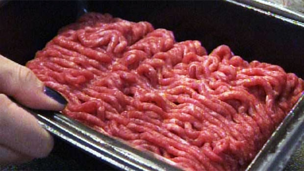 A woman holds a package of ground beef.