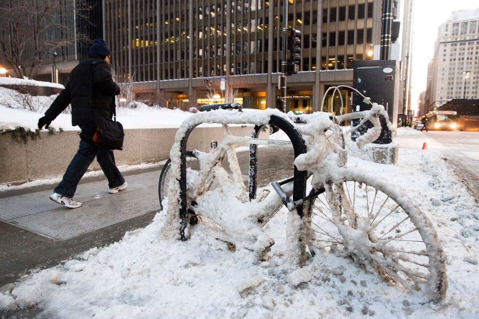 A man walks past a snow encrusted bicycle with wind chills nearing minus 30 Fahrenheit on Tuesday, Jan. 7, 2014, in downtown Chicago. (AP / Andrew A. Nelles)