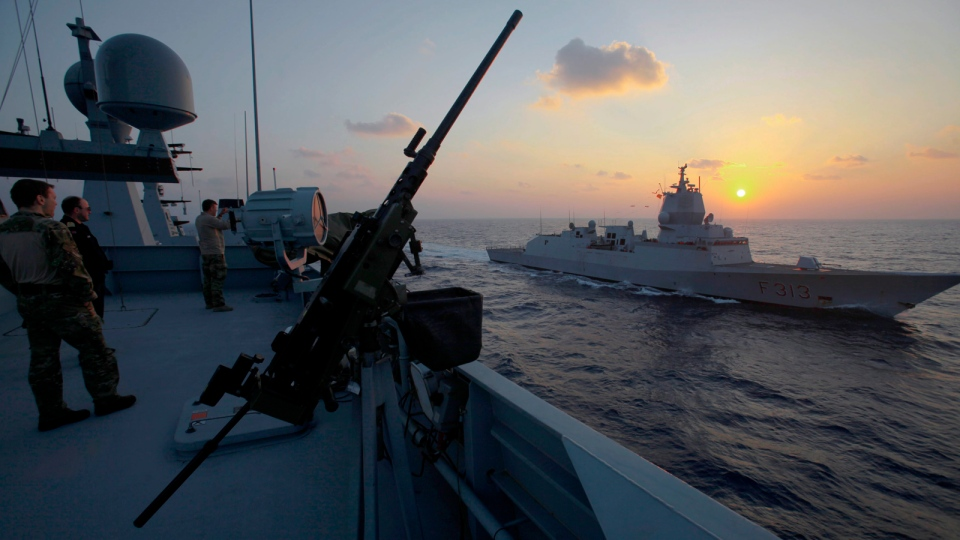 A crew member of the Danish warship Esbern Snare looks at the Norwegian warship 'Helge Ingstad' as they pass each other during a sunset at sea between Cyprus and Syria, Sunday, Jan. 5, 2014. (AP / Petros Karadjias)