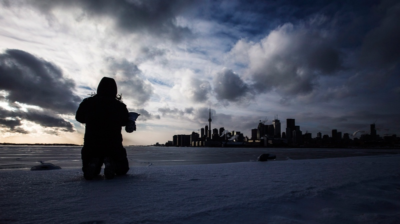 Joanna Leung takes pictures of the skyline and a frozen Lake Ontario during sub freezing weather in Toronto, Tuesday, Jan. 7, 2014. (Mark Blinch / THE CANADIAN PRESS)