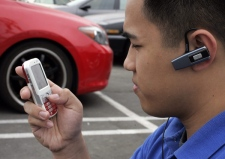 Chan Om uses his handsfree device for a cell phone next to his car in Mountain View, Calif., Tuesday, July 1, 2008. (AP / Paul Sakuma)