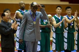 Dennis Rodman tips his hat as U.S. and North Korean basketball players applaud at the end of an exhibition basketball game at an indoor stadium in Pyongyang, North Korea on Wednesday, Jan. 8, 2014. (AP / Kim Kwang Hyon)